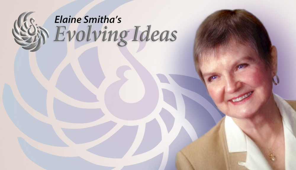 Elaine Smitha, Producer of Evolving Ideas. She has short brown hair, and is smiling at someone off screen. She is wearing a camel colored jacket and a white blouse.