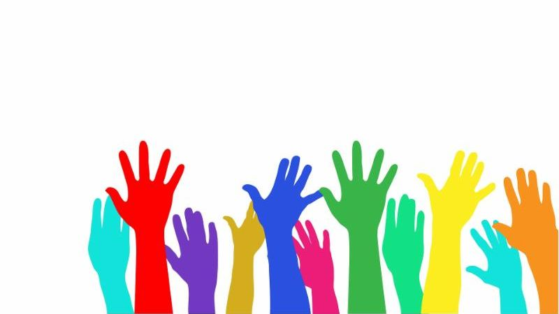 Multicolor hands raised together in a voting and volunteering gesture